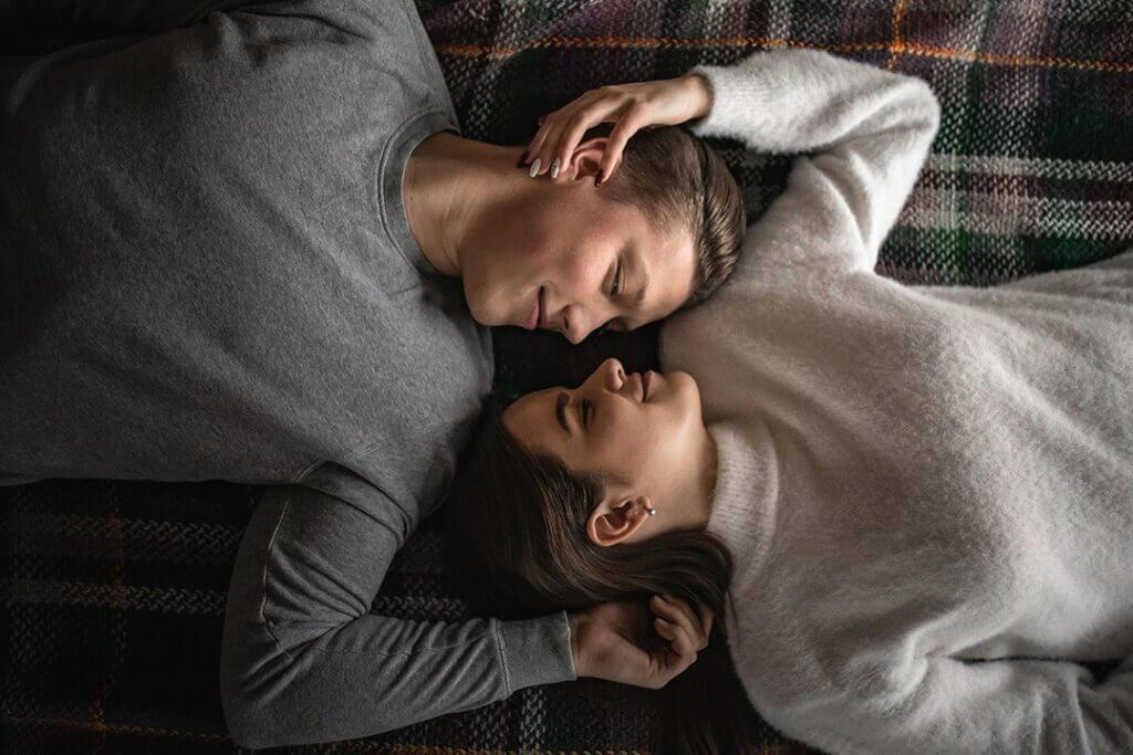 couple couché se regardent  dans les yeux heureux sexualité épanouis