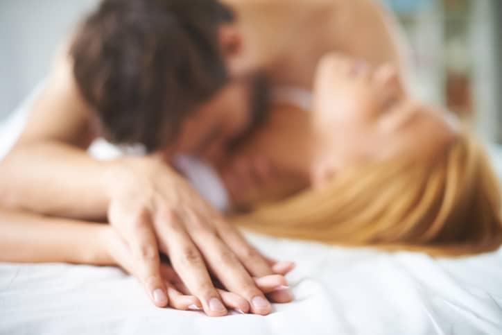 couple lit baisers dans le cou main dans la main sexualité