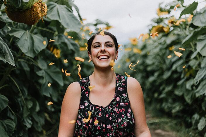 femme heureuse souriante entourée de pétales de fleurs dans un champ