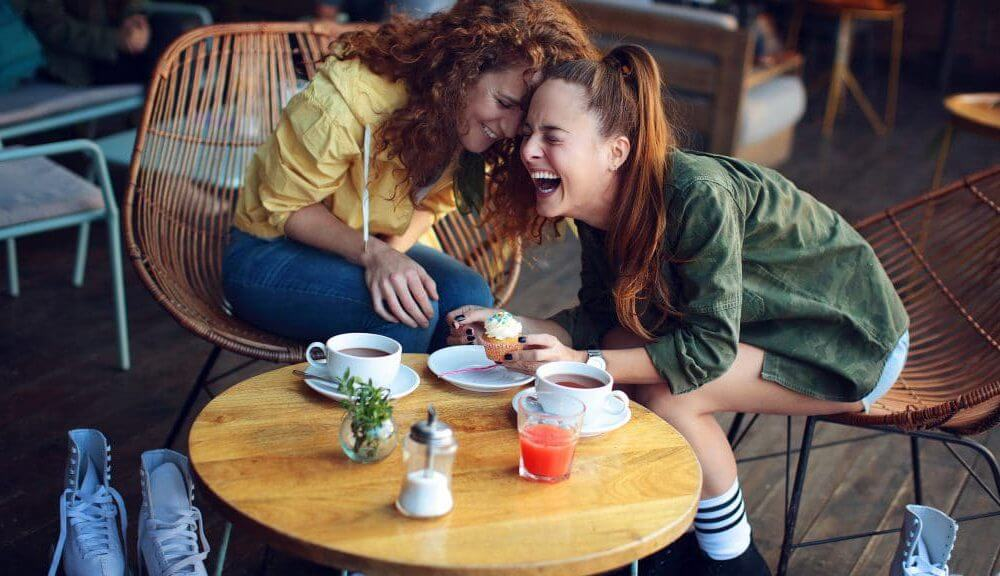 deux femmes en train de boire un café qui rigolent