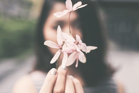 femme tenant une fleur dans la main